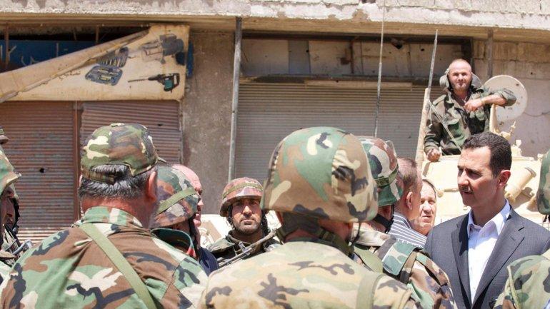 Al Assad saluda a las tropas leales a su dictadura. De fondo, una país derrumbado