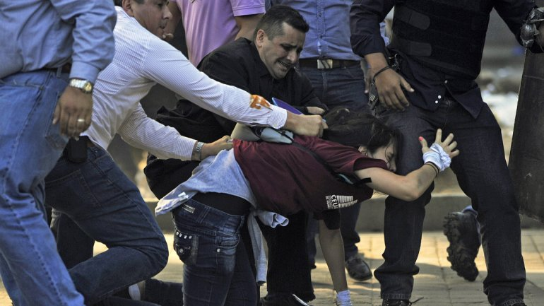 Una estudiante cae mientras grupos de oficiales de la CICPC (Policía Científica) quieren capturarla