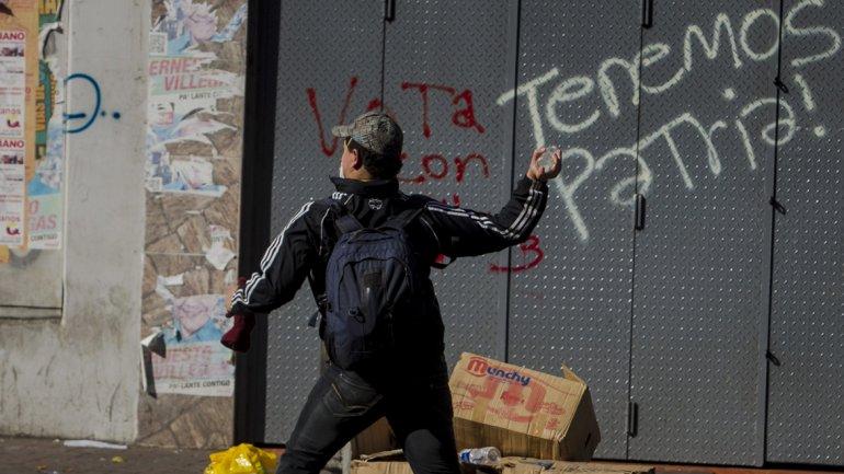 Un manifestante lanza una piedra contra el grupo policial