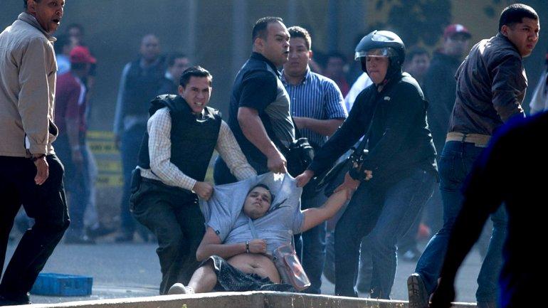 Un manifestante es arrastrado por fuerzas policiales