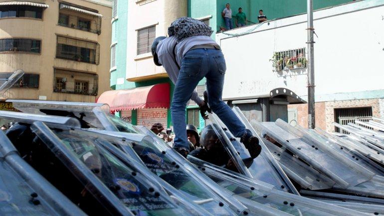 Un manifestante camina trepado sobre los escudos policiales en Caracas