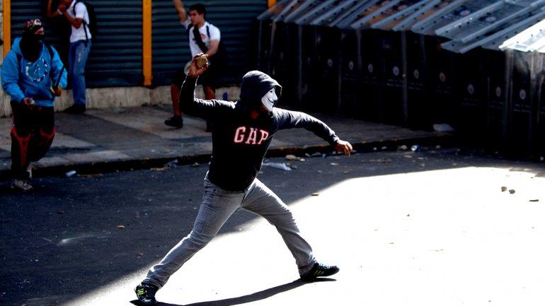 Escudado tras la máscara Anonymous, un manifestante lanza una piedra contra un muro de escudos policiales