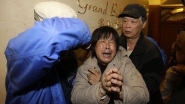 Familiares de los pasajeros del vuelo MH370 de Malaysia Airlines lloran tras escuchar el resultado de las investigaciones