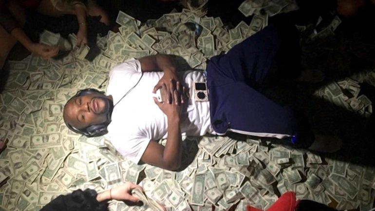Floyd Mayweather recostado sobre un colchón de dólares