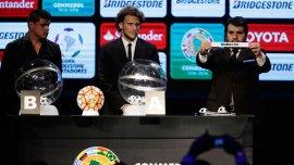 El director de competiciones de la Conmebol, Hugo Figueredo, muestra el nombre de un equipo junto a  Gustavo Bou y Diego Forlan durante el sorteo de la Copa Libertadores 2016