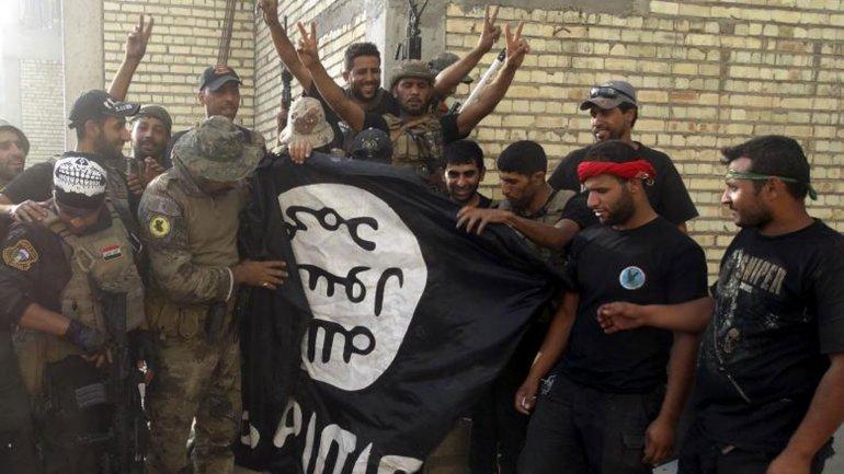 Soldados iraquíes sostienen una bandera que le fue arrebatada a los yihadistas del ISIS tras duros combates