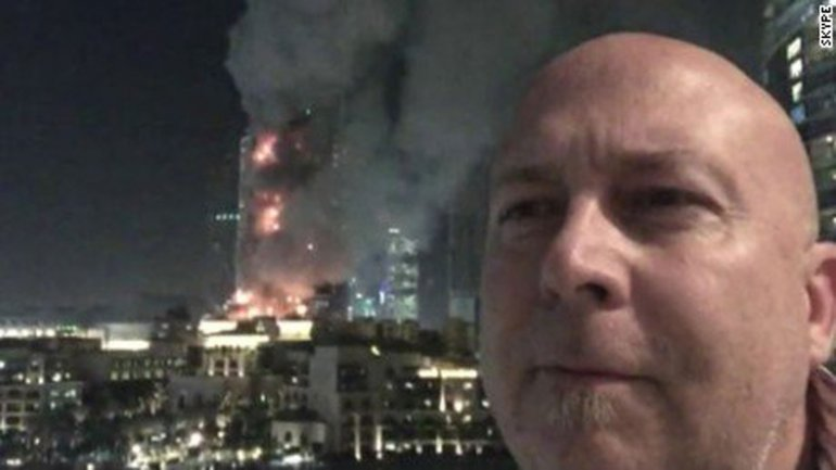 Otra seflie con el edificio en llamas de fondo
