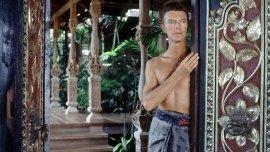 David Bowie utilizando un sarong al lado de una puerta balinesaen su villa en la exclusiva isla de Mustique, en el Caribe
