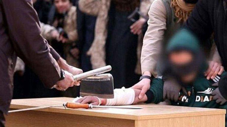 El momento en que un terrorista de ISIS le corta la mano a un hombre acusado de delinquir