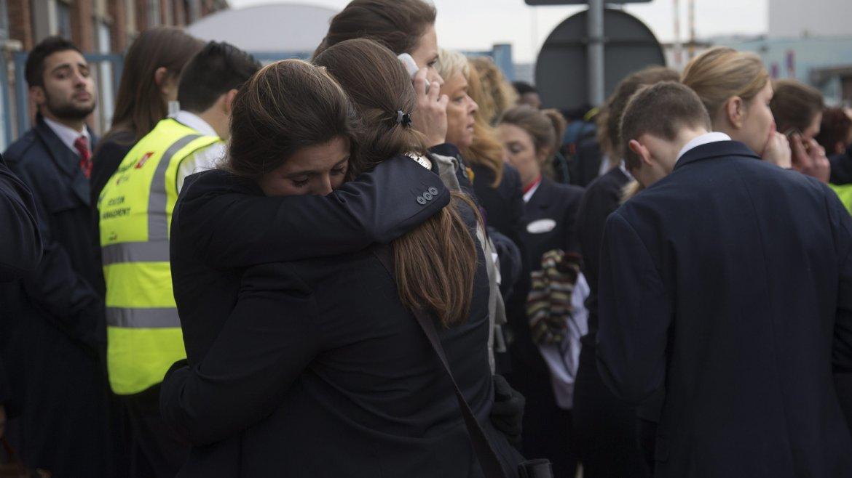 Dos azafatas se abrazan fuera del aeropuerto mientras son evacuadas