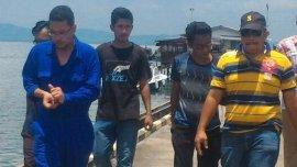 El capitán del barco, vestido de azul, es llevado a la comisaría para ser interrogado