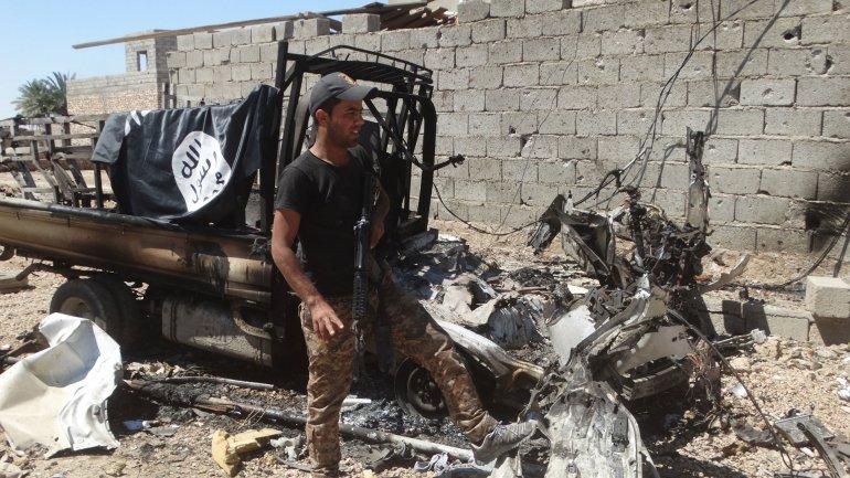 Un soldado iraquí posa junto a un vehículo destruido del Estado Islámico en la ciudad de Hit