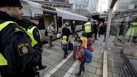 Menores refugiados, controlados por la policía danesa en el puente entre Dinamarca y Suecia.