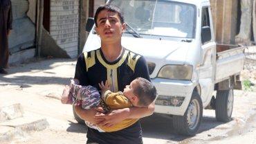Un adolescente huye con su pequeño hermano en medio de los ataques contra el barrio rebelde de Al Fardous, Alepo