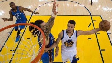 Stephen Curry, figura de Golden State con 28 puntos, frente a Steve Adams, el neozelandés de Oklahoma City Thunder