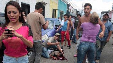Vecinos y familiares de una víctima de la violencia callejera en la ciudad de San Cristóbal se desesperan por auxiliarla.