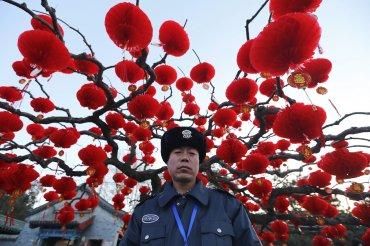Un policía, rodeado de farolillos rojos, vigila el parque Ditan en Beijing durante las celebraciones del Año Nuevo chino