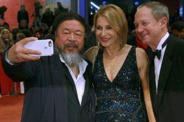 El artista chino Ai Weiwei posa para una selfie junto al Embajador de Estados Unidos en Alemania, John Emerson y su esposa