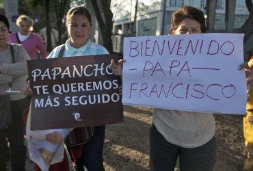Dos fieles mexicanas sostienen pancartas de bienvenida al Papa Francisco.