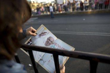 Una mujer sostiene una foto de Francisco tras las vallas que separaron a los fieles del Sumo Pontífice.