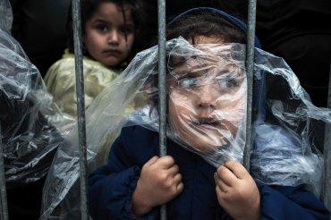 Primer premio de la gategoría Gente, Matic Zorman.  El niño se cubre con un impermeable mientras espera para registrarse en un campo de refugiados en Presevo, Serbia