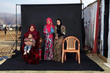 Tercer premio de la categoría Gente, Dario Mitidieri. Retrato de una familia de refugiados sirios en un campamento en el valle de la Bekaa, Líbano. La silla vacía en la fotografía representa un miembro de la familia que ha muerto en la guerra