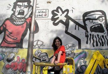 Los graffitis que nacen de los encuentros no siempre son reivindicativos o feministas. Los ejemplos van desde una mujer amordazada y atada de manos hasta una simple mariposa de colores. (La graffitera Chanel Arif subiendo con la grúa para pintar su mural en el encuentro de 2015 en El Cairo, bautizado WOW Unchained)