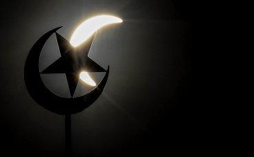 El eclipse a través de la medialuna y la estrella musulmanas en la mezquita de Kuala Lumpur, la mayor ciudad de Malasia.