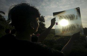 Una persona observa el eclipse a través de una radiografía, para proteger sus ojos, en Silaut, provincia de Sumatra, Indonesia.