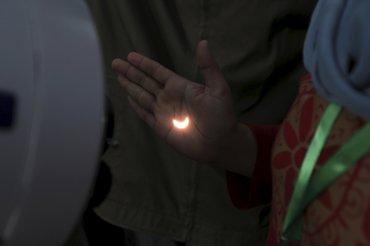 La luz del eclipse solar se refleja en la mano de una persona frente a un telescopio en el puente Ampera, sobre el río Musi en Palembang, sur de Sumatra, Indonesia.