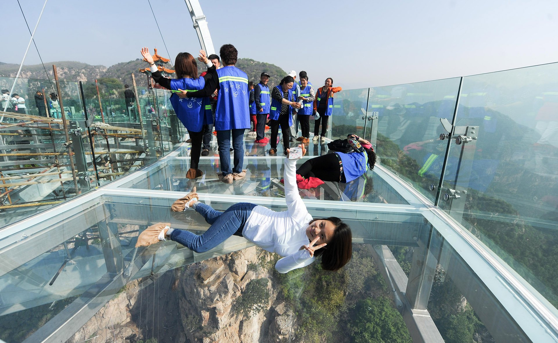 El piso de vidrio permite a los turistas tomarse fotos con el vacío bajo sus pies