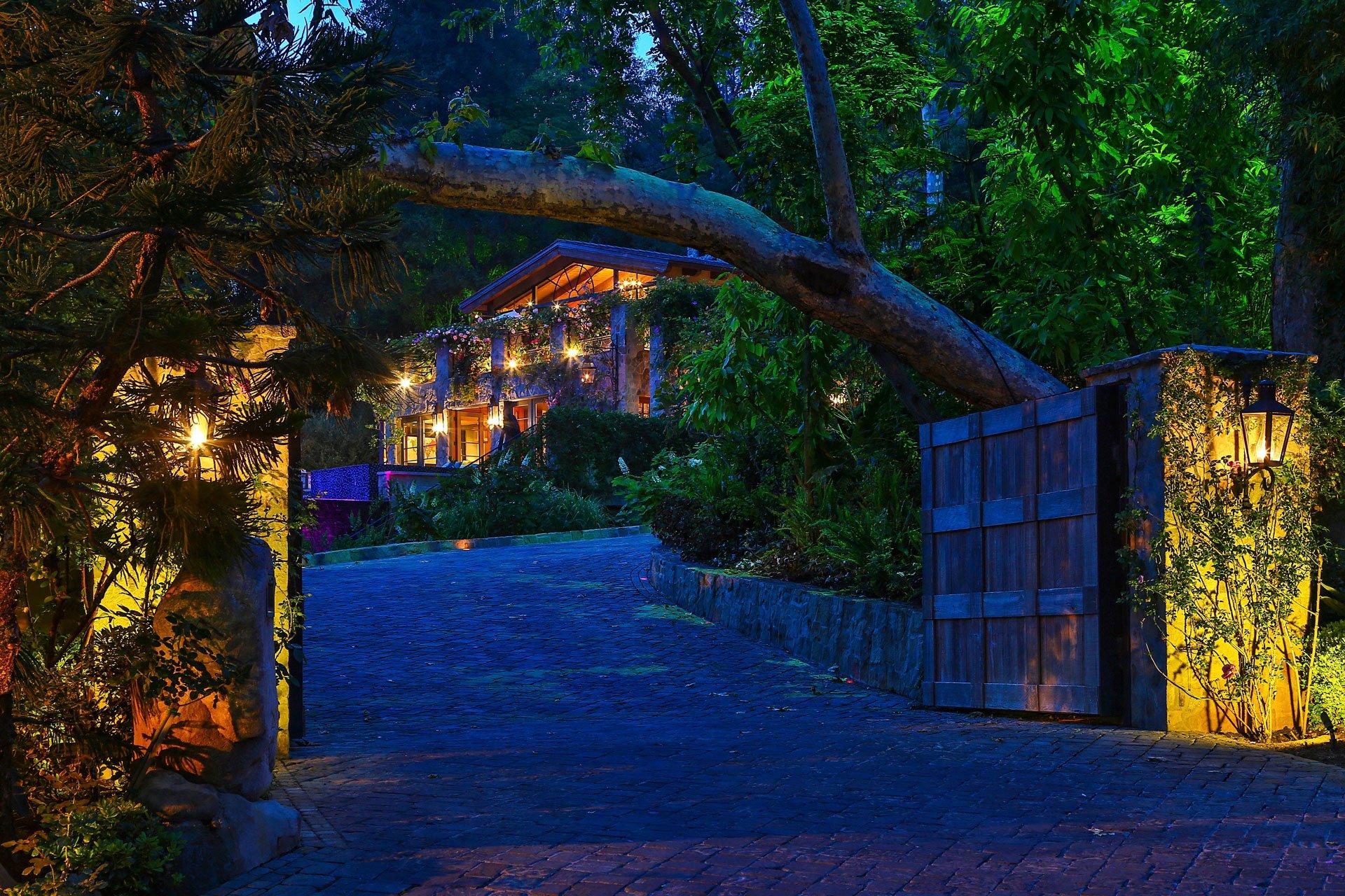 La entrada a la mansión, de noche. La iluminación forma parte del detallado decorado de la vivienda